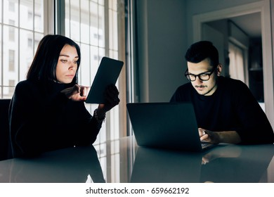 Young woman and young woman indoor in apartment using computer and tablet, face illuminated by screen light - technology, co workers, phubbing concept