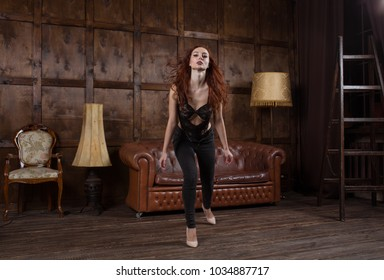 young woman indulges and entertains herself in Loft style interior. model dances in the Urban apartment.