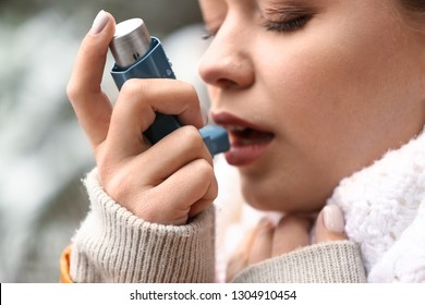 Young woman with inhaler having asthma attack outdoors, closeup