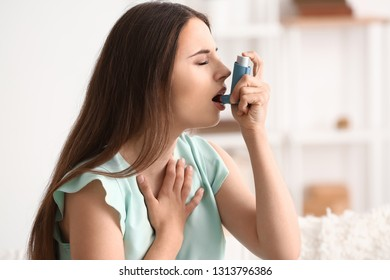 Young woman with inhaler having asthma attack at home