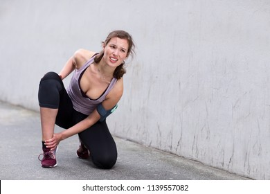 young woman with an injured ankle while running