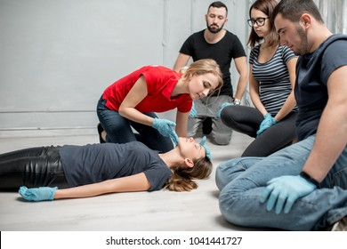 Young woman instructor showing how to lay down a woman during the first medical aid training indoors