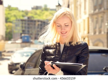 Young woman insurance agent or sales agent prepares documents outdoors on city background. Business woman with folder of documents in her hands outdoors. Woman conducting a survey and writing data.