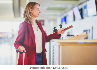 Young woman in international airport at check-in counter giving her passport to officer