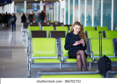 Young woman in international airport, checking her phone while waiting for her flight