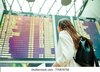 Young woman in international airport looking at the flight information board, checking her flight