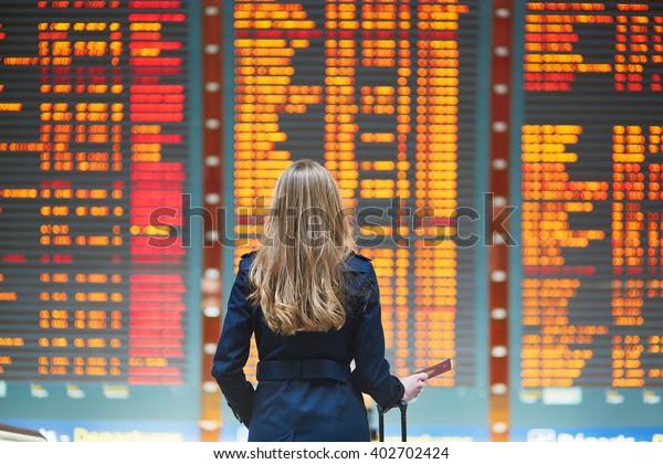Junge Frau am internationalen Flughafen, die sich die Fluginformationsstelle anschaut, den Reisepass in der Hand hält und ihren Flug überprüft