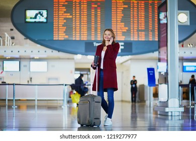 Young woman in international airport with luggage, speaking on the phone, waiting for her flight