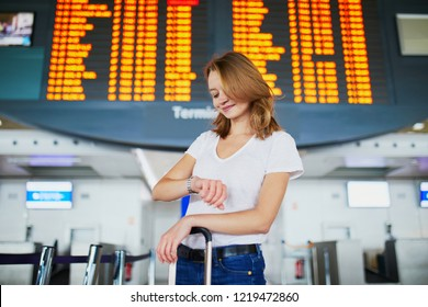 Young woman in international airport with luggage near flight information display, waiting for her flight and looking at her watch
