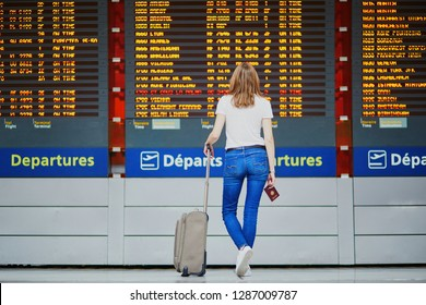 Young woman in international airport with luggage and passport near flight information display