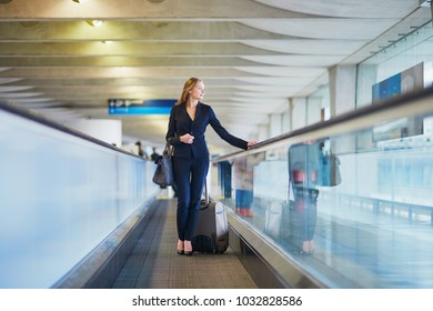 Young woman in international airport on travelator
