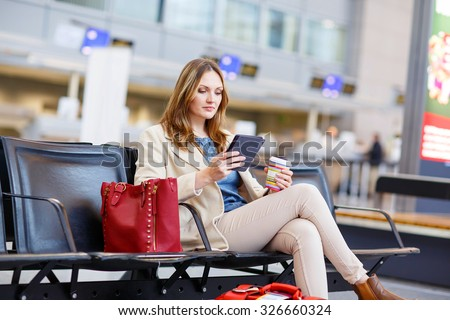 Young woman at international airport, reading her ebook and drinking coffee while waiting for her flight on business trip. Female passenger at terminal, indoors.