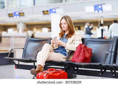 Young woman at international airport sitting waiting for canceled or delayed flight. Female passenger at terminal, indoors.  Travel, business, people concept.