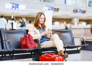 Young woman at international airport sitting waiting for cancelled or delayed flight. Female passenger at terminal, indoors.  Travel, business, people concept.