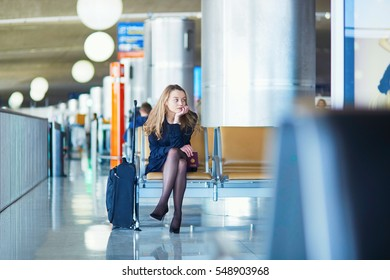 Young woman in international airport, waiting for her flight, looking upset or worried. Missed, canceled or delayed flight concept