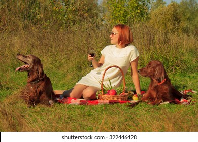 Young woman and Irish setters at the picnic