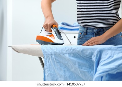 Young woman ironing clothes on board at home, closeup