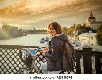 A young woman in a jacket uses a navigator riding around the city on a bicycle, Moscow, an urban lifestyle