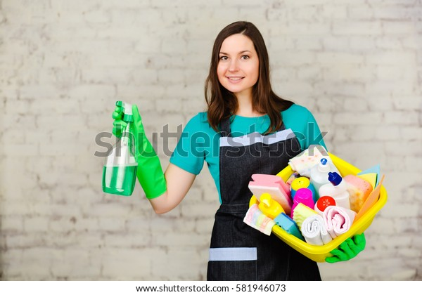 Young woman janitor cleaning with spray and detergent, standing in a modern office smiling and looking at camera