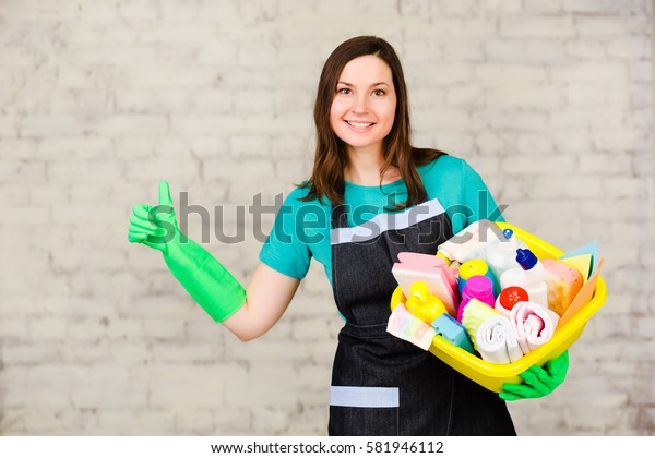 Young woman janitor holding bucket with many colorful detergent for cleaning office. Worker cleaning service. On the soft-focus background a white brick wall