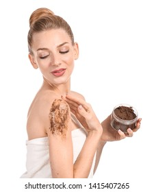 Young woman with jar of body scrub on white background