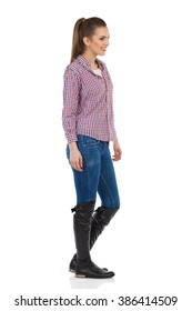 Young woman in jeans, black boots and lumberjack shirt standing and looking away. Side view. Full length studio shot isolated on white.