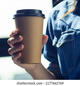 Young woman in jeans with disposable coffee cup. Youth, modern lifestyle. Coffee break, cosy relaxing moment.