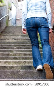 young woman in jeans going up steep stairs