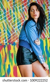 Young woman in jeans jacket and leather short colorful background
