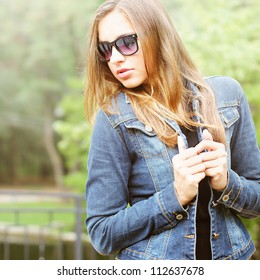 Young woman in jeans jacket walking outdoor