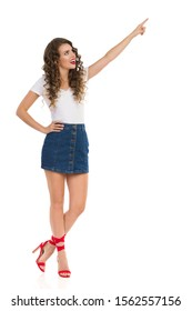 Young woman in jeans mini skirt, white top and red high heels is pointing up, looking away and talking. Full length studio shot isolated on white.