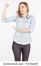 young woman in jeans shirt shows with your finger the muscles in the hand. Image Isolated on white background