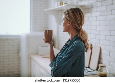 Young woman in jeans shirt standing in the kitchen and thoughtfully looking into the distance while holding a cup of tea