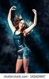 young woman in jeans shorts dancing, studio shot