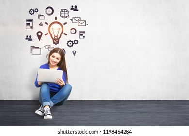 Young woman in jeans and sweater sitting on concrete floor of white room with her laptop, looking at the screen and smiling. Concrete wall with internet business idea icons. Mock up