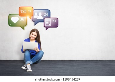 Young woman in jeans and sweater sitting on concrete floor of white room with her laptop, looking at the screen and smiling. Concrete wall with colorful social media icons. Mock up