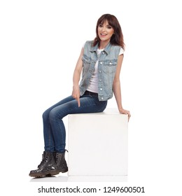 Young woman in jeans vest and black boots is sitting relaxed on a white box, pointing down and talking. Full length studio shot on white background.