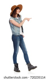 Young woman in jeans vest, black boots and brown suede hat is standing, smiling, looking away and pointing. Side view. Full length studio shot isolated on white.