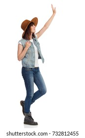 Young woman in jeans vest, black boots and brown suede hat is standing with arm raised, looking away and waving hand. Side view. Full length studio shot isolated on white.