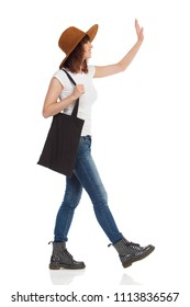 Young woman in jeans vest, boots and brown suede hat is walking, holding black bag on her shoulder, looking away and waving hand. Side view. Full length studio shot isolated.