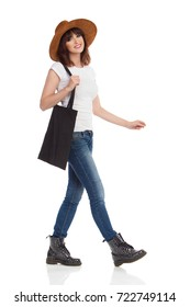 Young woman in jeans vest, boots and brown suede hat is walking, holding black bag on her shoulder and looking at camera. Side view. Full length studio shot isolated on white.
