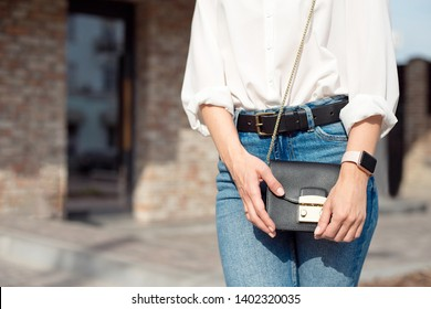 Young woman in jeans and a white shirt standing on the street holding a lady's bag in which lies her smart phone and wallet.