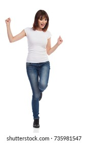 Young woman in jeans and white t-shirt is dancing on one leg and shouting. Front view. Full length studio shot isolated on white.