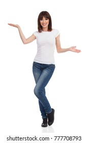 Young woman in jeans, white t-shirt and sneakers is standing with hands raised, looking at camera, smiling and presenting. Full length studio shot isolated.