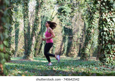 young woman jogger in autumn woods