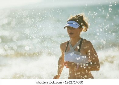 young woman jogger in fitness clothes on the seashore in the evening running. running out from same workout routine. 30 something years old woman having running workout at beautiful seashore