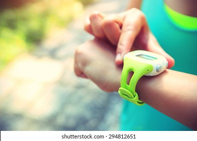 Young woman jogger ready to run set and looking at sports smart watch, checking performance or heart rate pulse trace. Sport and fitness outdoors on forest trail.