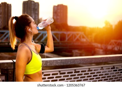 Young woman jogger resting drinking water