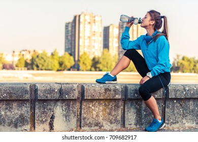 Young woman jogger resting drinking water by the river