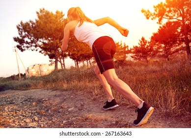 Young woman jogger running on the road in morning park. Active female athlete during outdoors workout at sunset.